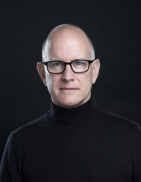 Randy Barbato wearing a black turtleneck against a dark background