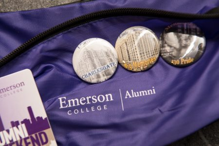Table with buttons and purple tablecloth with text that reads Emerson College Alumni