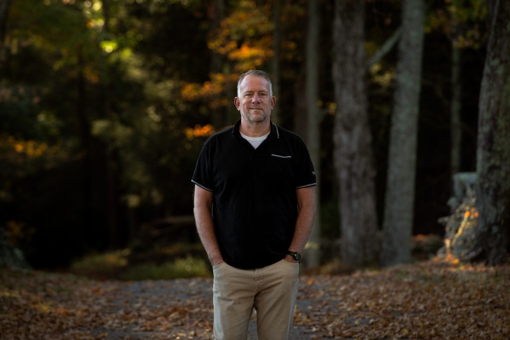 Philip Finch, MA '97 with the woods in the background  | Photo by Derek Palmer