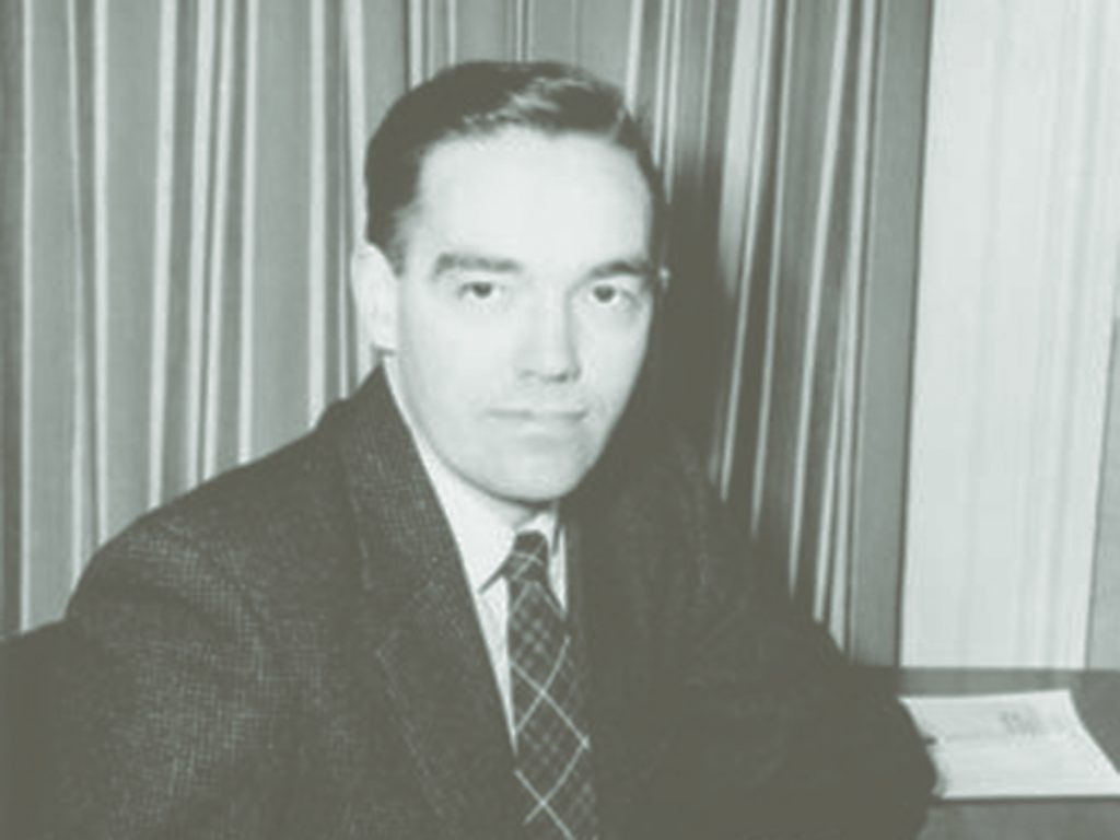 Charles Klim wearing a suit sitting at a desk
