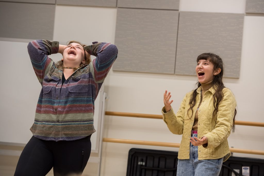 Two female students in a scene in an improv class