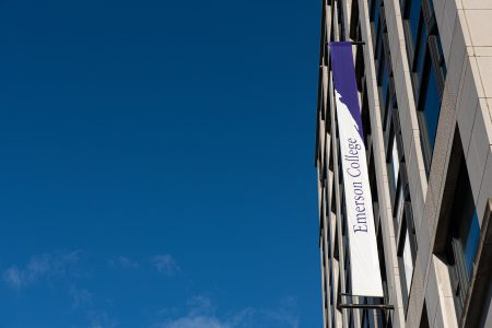 shot of Emerson College building with purple and white banners against a blue sky