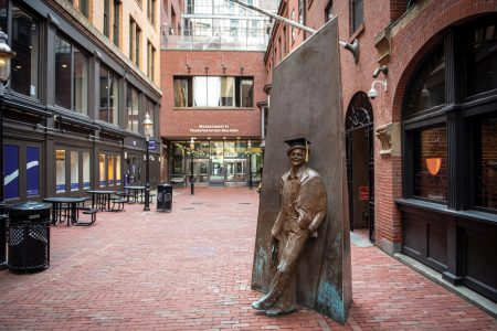 Norman Lear statue with a graduation cap in Boylston Place alley
