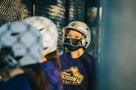 Softball player wearing a helmet and an Emerson Lions t-shirt standing by a fence during softball practice