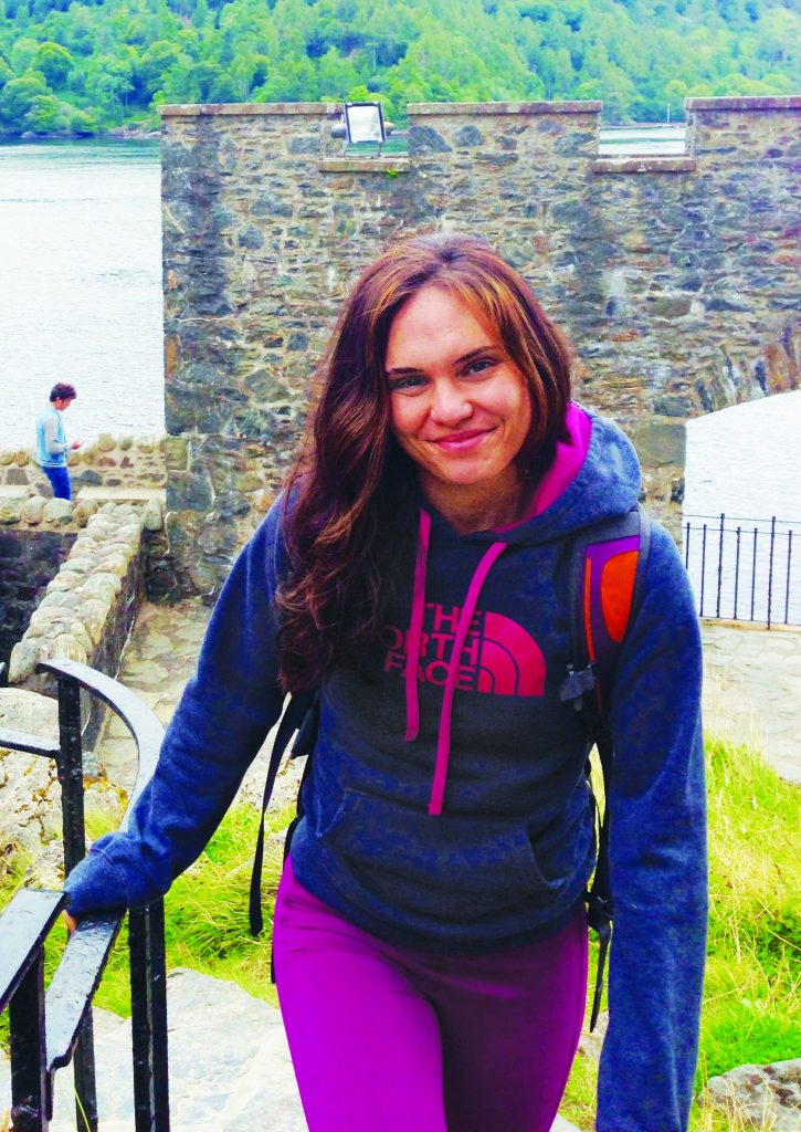 Photo of Laura Lewis climbing stairs in Scotland wearing a North Face hoodie
