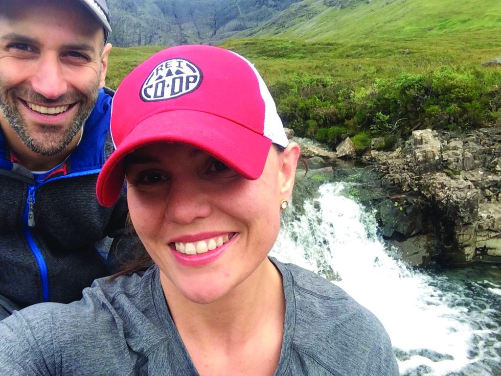Laura Levis and her husband standing in front of a waterfall